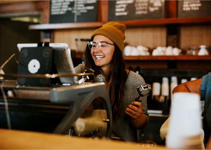 chica-con-gafas-poniendo-un-cafe-y-sonriendo
